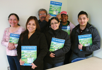 Group of smiling ESL students holding their workbooks