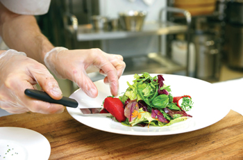 Culinary student preparing a salad on a bowl for serving