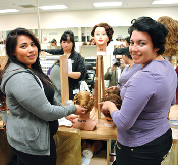 Cosmetology students practicing hair styling on mannequins