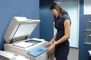 Woman standing over and operating a photocopier